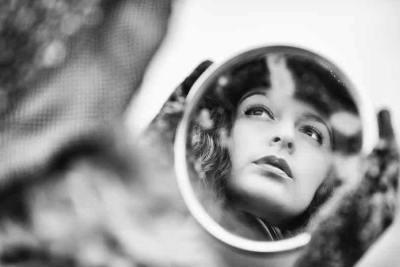 Face's reflection on mirror of beautiful pensive woman, retro styled image in black and white.