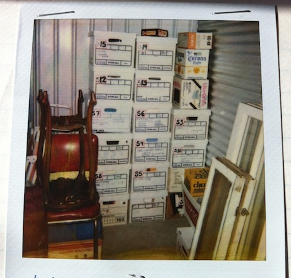 A polaroid of my very organized storage unit with labels on the boxes corresponding to an elaborate notebook detailing contents of each – note the stacked up windows rescued from dumpsters and construction sites.
