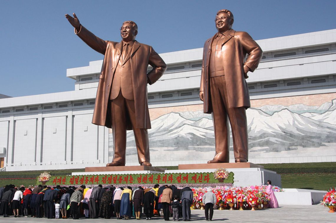 1280px-The_statues_of_Kim_Il_Sung_and_Kim_Jong_Il_on_Mansu_Hill_in_Pyongyang_(april_2012)