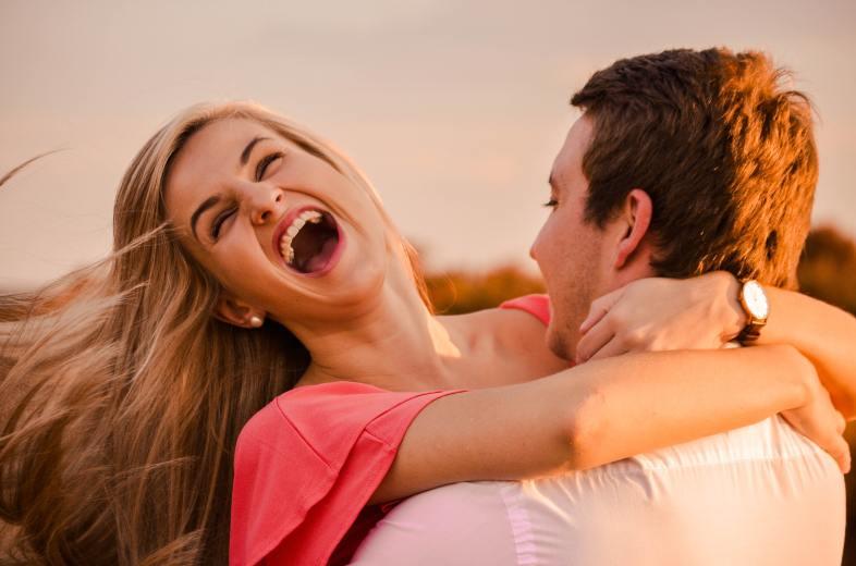 man hugging woman while smiling