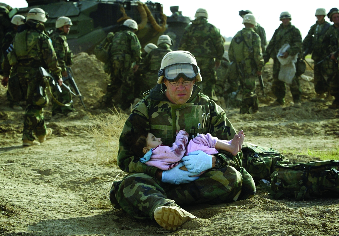 U.S. Navy Hospital Corpsman HM1 Richard Barnett, assigned to the 1st Marine Division, holds an Iraqi child in central Iraq in this March 29, 2003 file photo. Confused front line crossfire ripped apart an Iraqi family after local soldiers appeared to force civilians towards positions held by U.S. Marines. March 20 marks the one year anniversary of the beginning of the U.S. led war against Iraq. The war started on March 20 Baghdad local time, March 19 Washington D.C. local time. REUTERS/Damir Sagolj HIGHEST QUALITY AVAILABLE - RTR1ADKJ