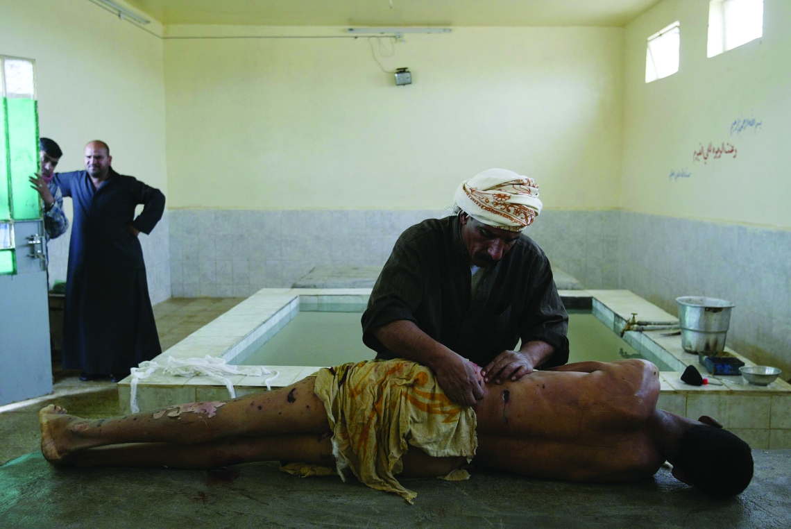 FILE -- In this photo by Joan Silva, Ali Hadi, a professional body washer, prepares the body of a bombing victim for Muslim burial as the man's relatives watch in Najaf, Iraq, on March 3, 2004. Silva was severely wounded on Oct. 23, 2010, when he stepped on a mine while on patrol with American soldiers in southern Afghanistan. (Joao Silva/The New York Times)