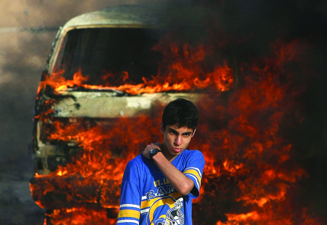 GAZA CITY, -: A Palestinian youth stands in front of a burning vehicle during clashes between rival Fatah and Hamas in Gaza City, 14 May 2007. Two Palestinians were killed in fresh fighting between rival Fatah and Hamas gunmen today despite a truce aimed at ending the worst factional violence since a unity government took office. AFP PHOTO/MOHAMMED ABED (Photo credit should read MOHAMMED ABED/AFP/Getty Images)