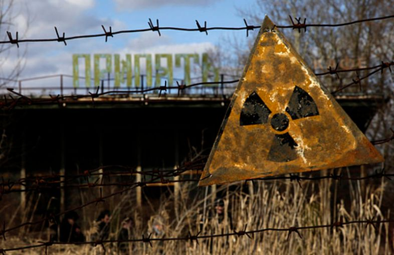 A radioactive sign hangs on barbed wire outside a café in Pripyat via wiki commons