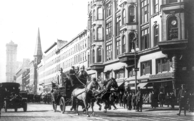 A horse-drawn fire engine en route to the burning factory