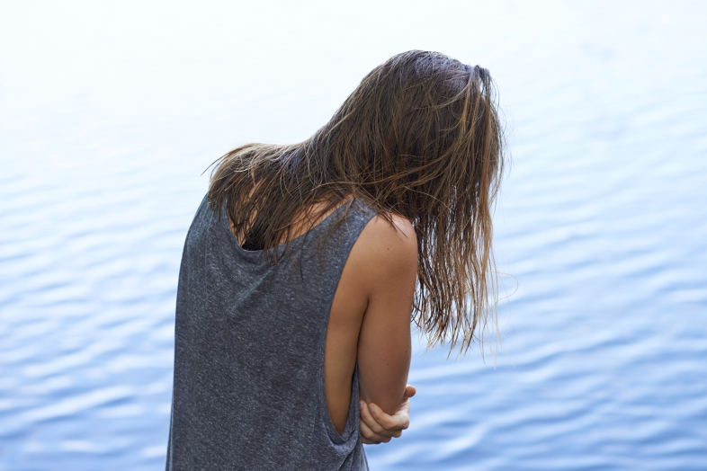 Rearview of a woman hugging herself with rippled water in the background