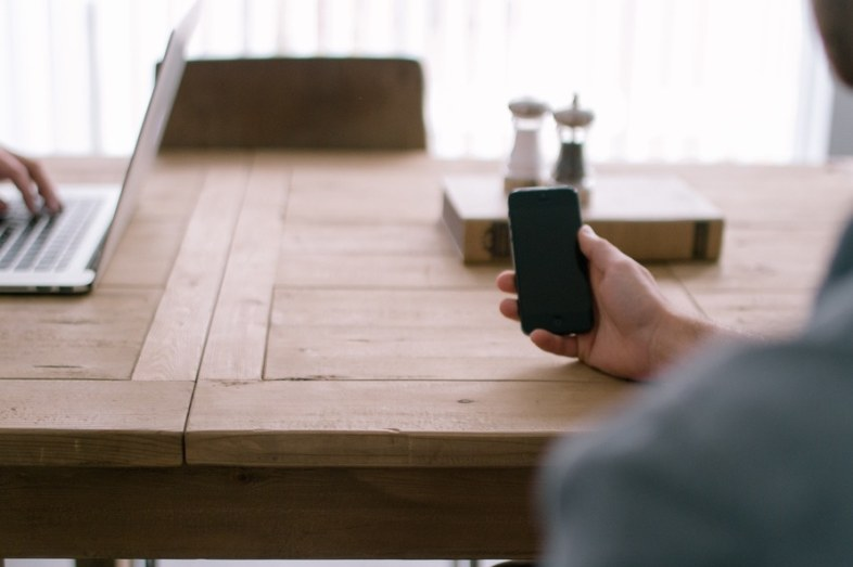 person-smartphone-office-table-large
