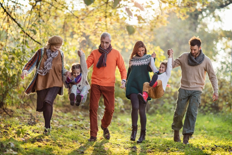 Playful multi-generation family having fun during autumn day in nature while holding hands and swinging small kids.