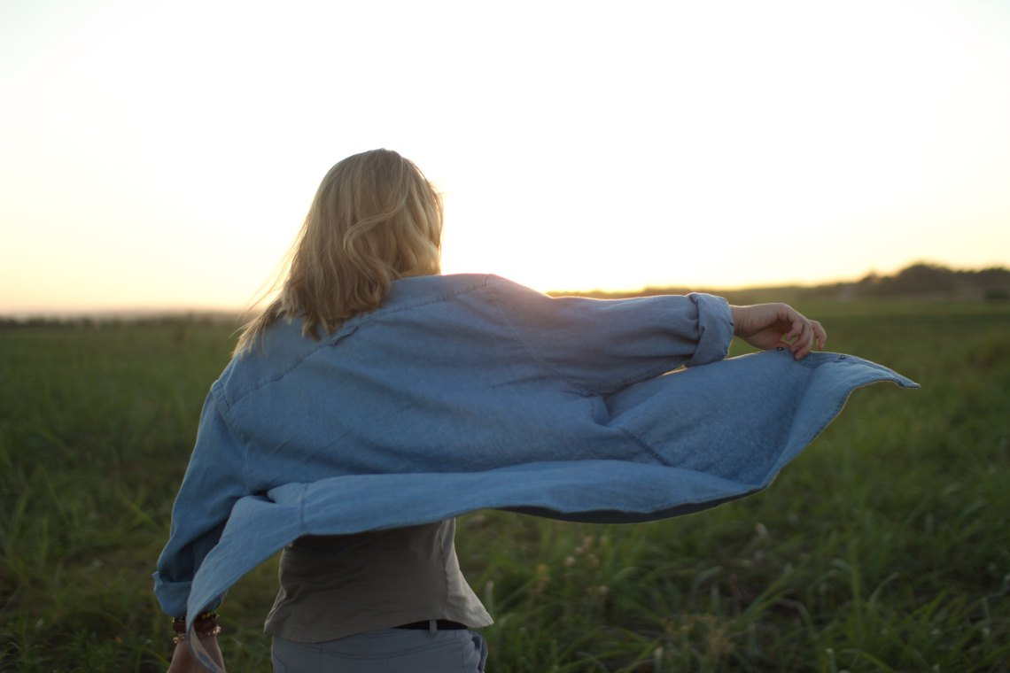 Young woman with shirt blowing in wind
