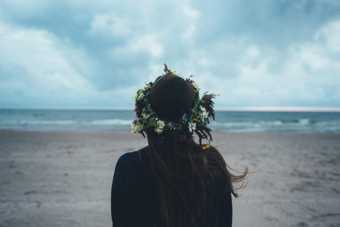 Woman with flower crown by beach