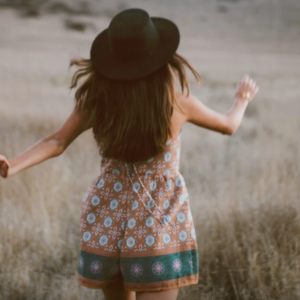 Girl with fedora walking in field