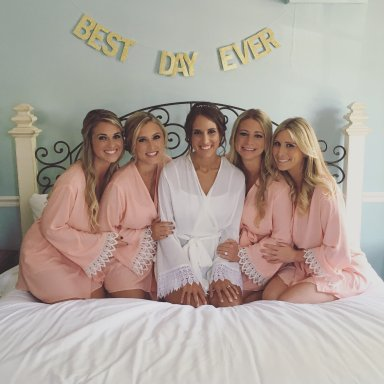 Bridesmaids and bride sitting on a bed, celebrating a wedding
