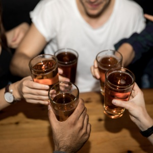 Friends all cheers with beer in hand at a bar