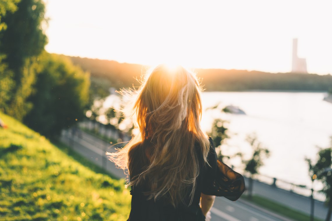 Blonde woman in front of sun