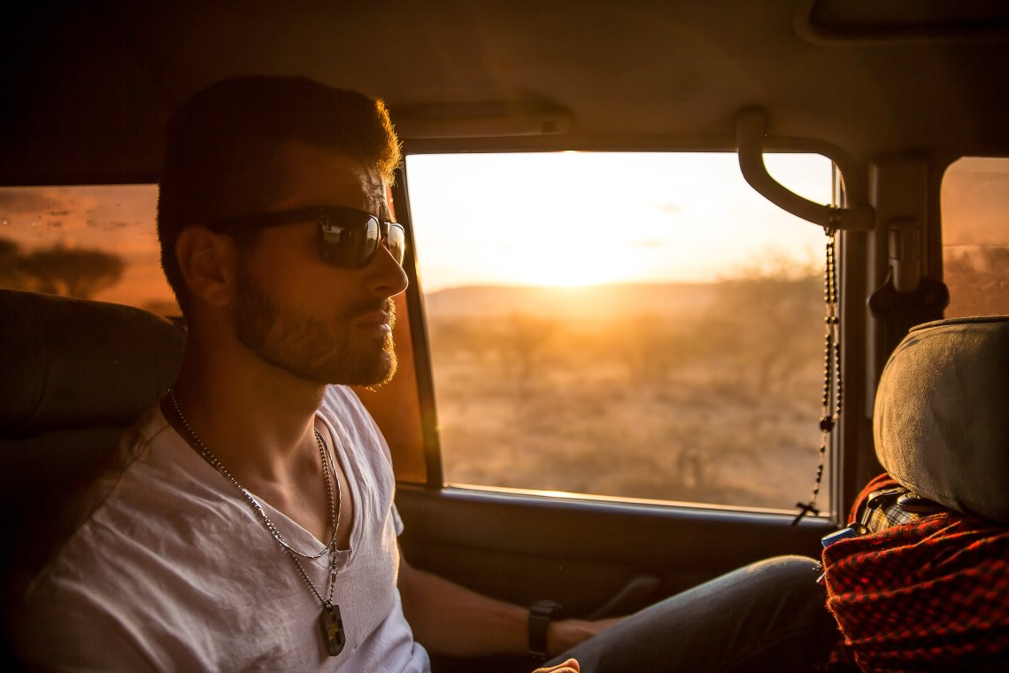 Handsome man riding in car, sunset behind him.