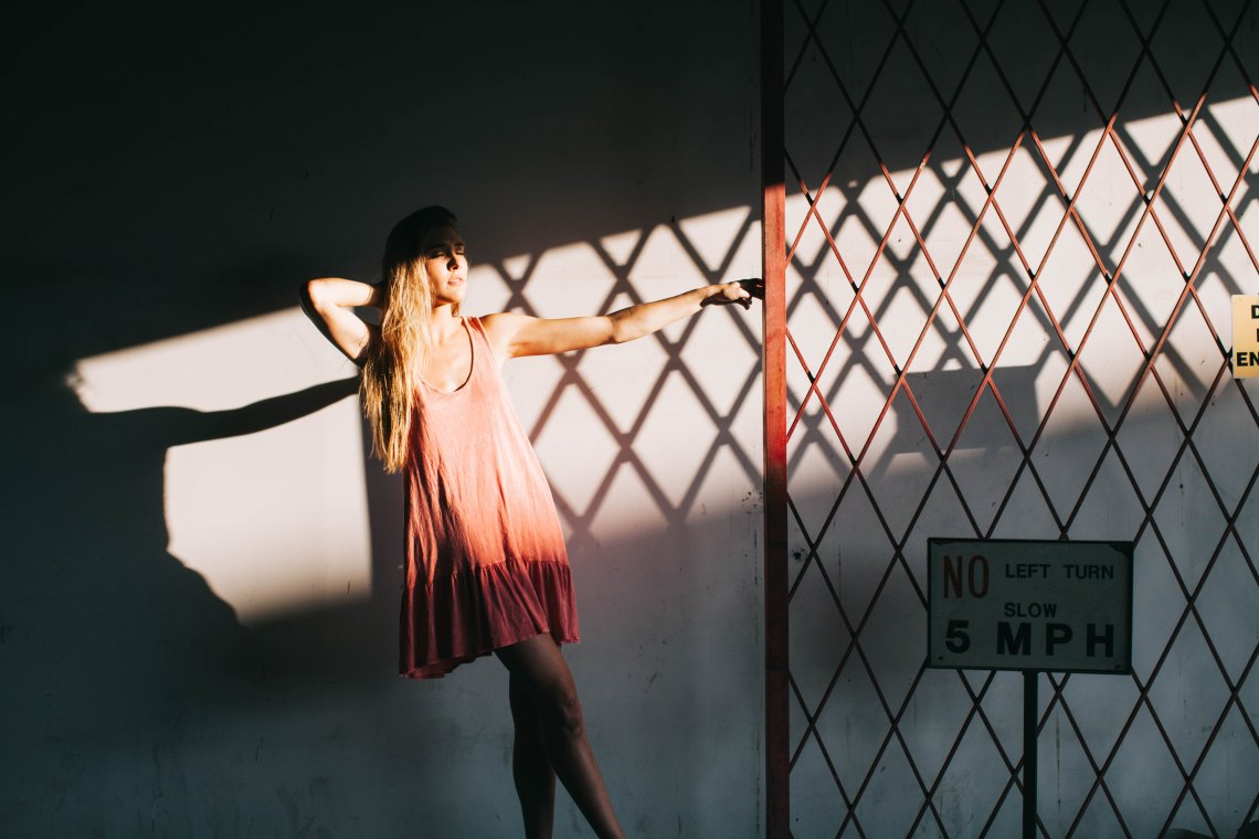 Girl in pink dress in front of shadows