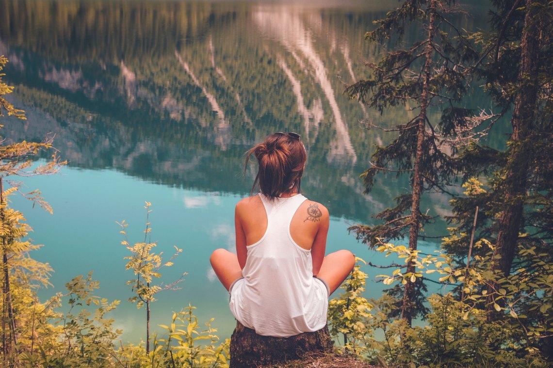 Girl sitting on cliff thinking