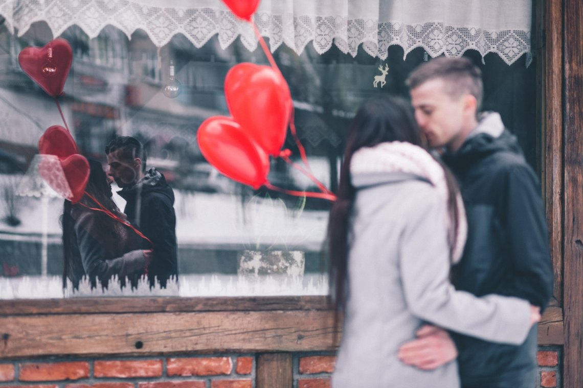 Couple kissing in front of window heart balloons