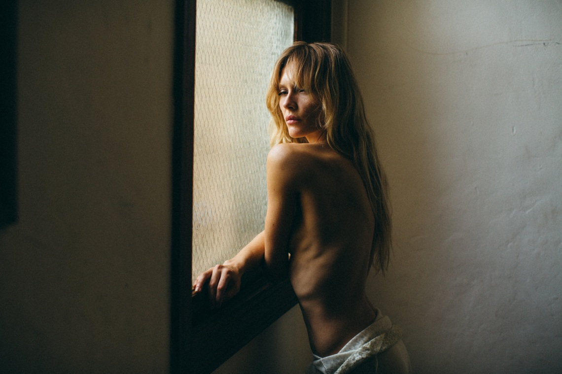 Woman looks out in a dark room