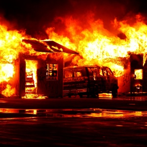 A van is on fire and there is chaos and destruction