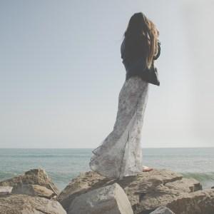 Woman in long skirt standing on beach rocks
