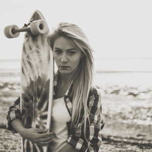 Woman with skateboard on beach