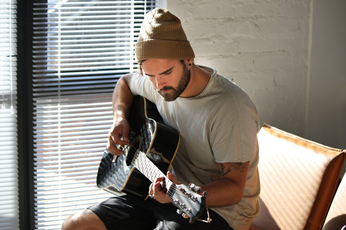 Guy in beanie playing guitar