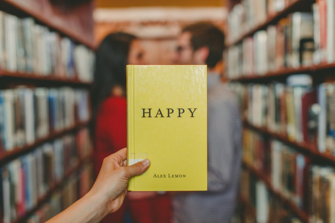 """someone holds up a book that says """"happy"""" in a library"""