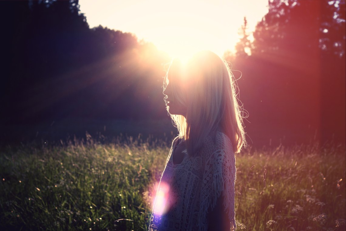 Silhouette blonde woman in front of sun