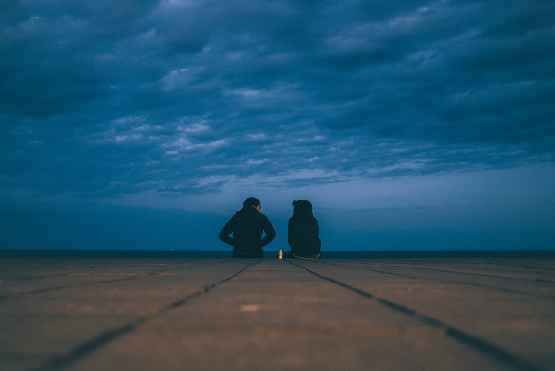 Couple sitting in front of dark sky