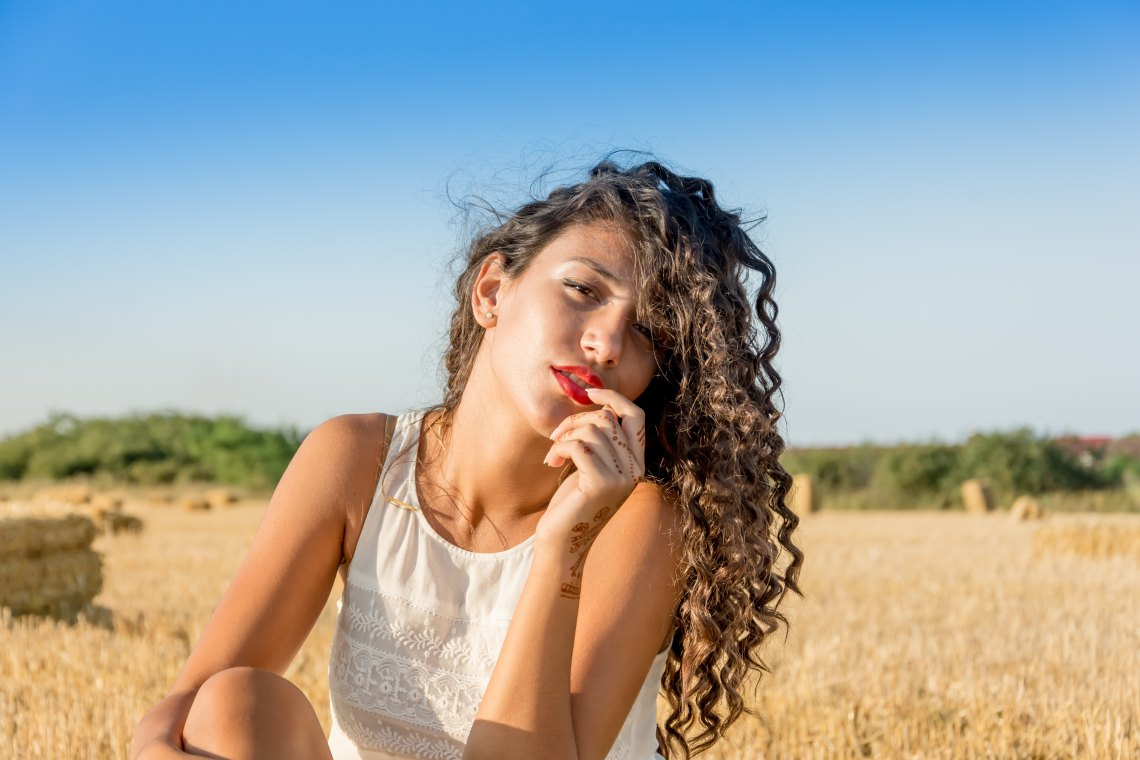 Girl with dark curly hair red lipstick in field