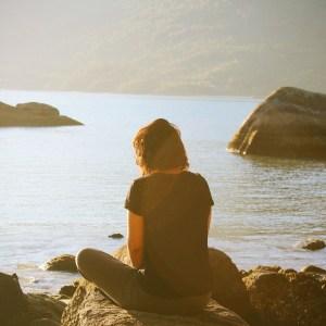 Woman sitting on rocks looking at beach