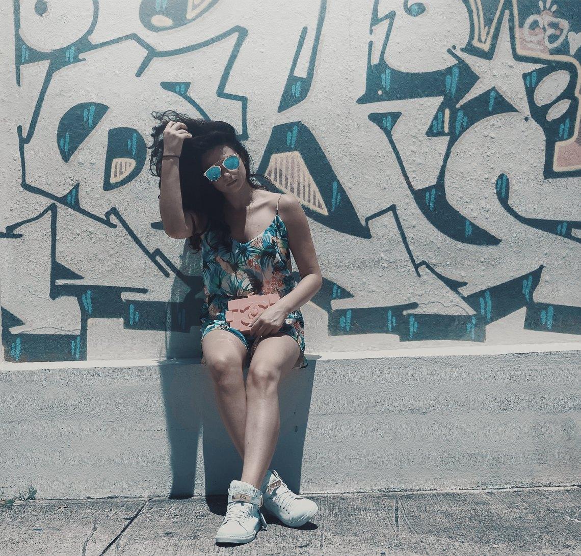girl sitting in front of grafitti