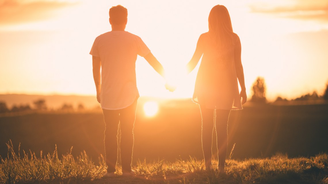 Couple holding hands in front of sunset