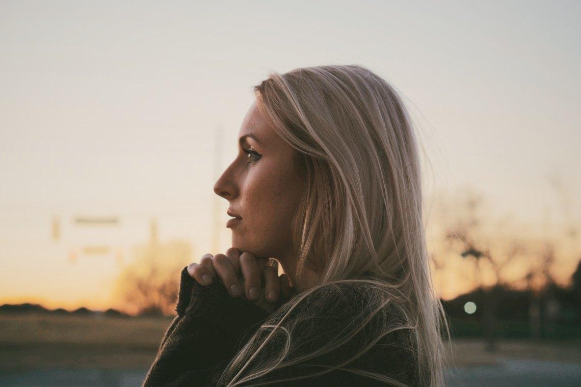 Blonde woman at sunset praying