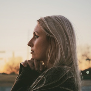 Blonde woman at sunset praying