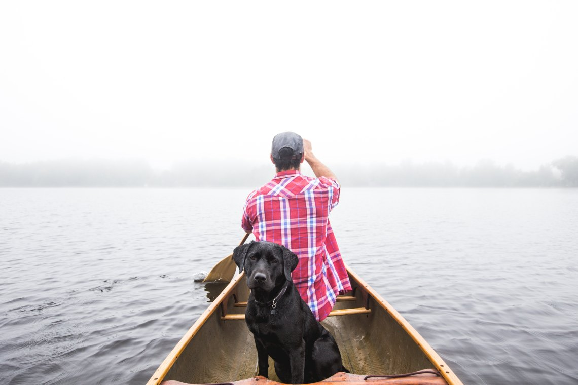 Guy in canoe with dog