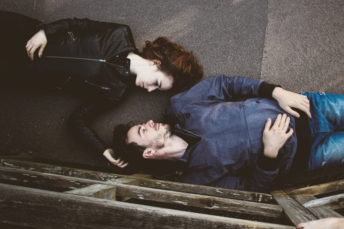 Couple laying on pavement together