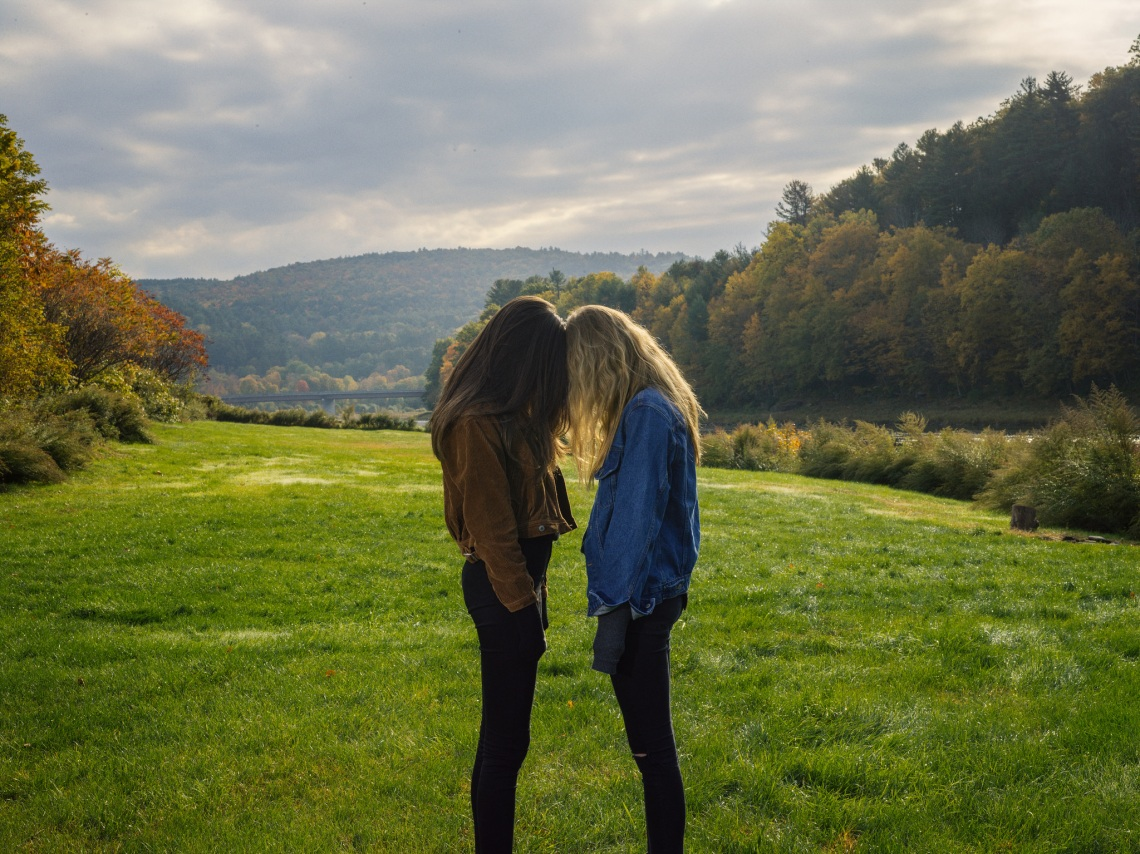 Two girls stand side-by-side in a field