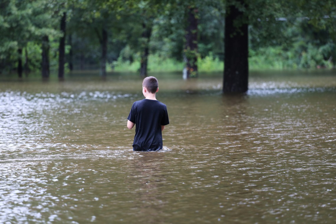 Boy stands in the flood waters during Hurricane Harvey in Texas