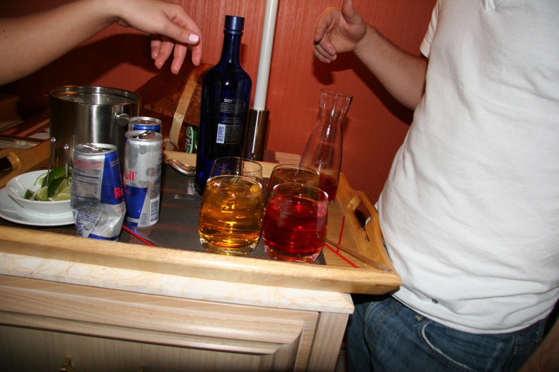 Two friends talk over a multitude of alcoholic beverages and red bull