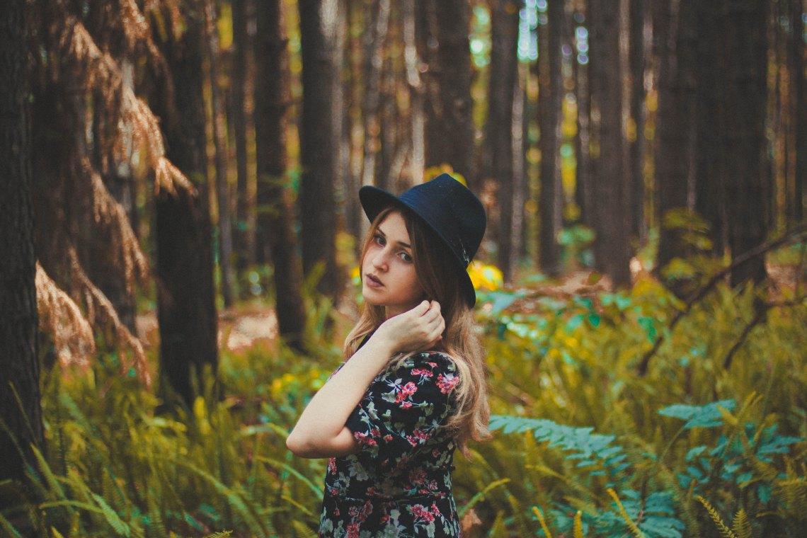 Girl in fedora in woods