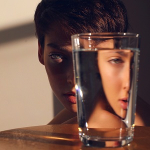 girl hiding behind drinking glass, scared to feel