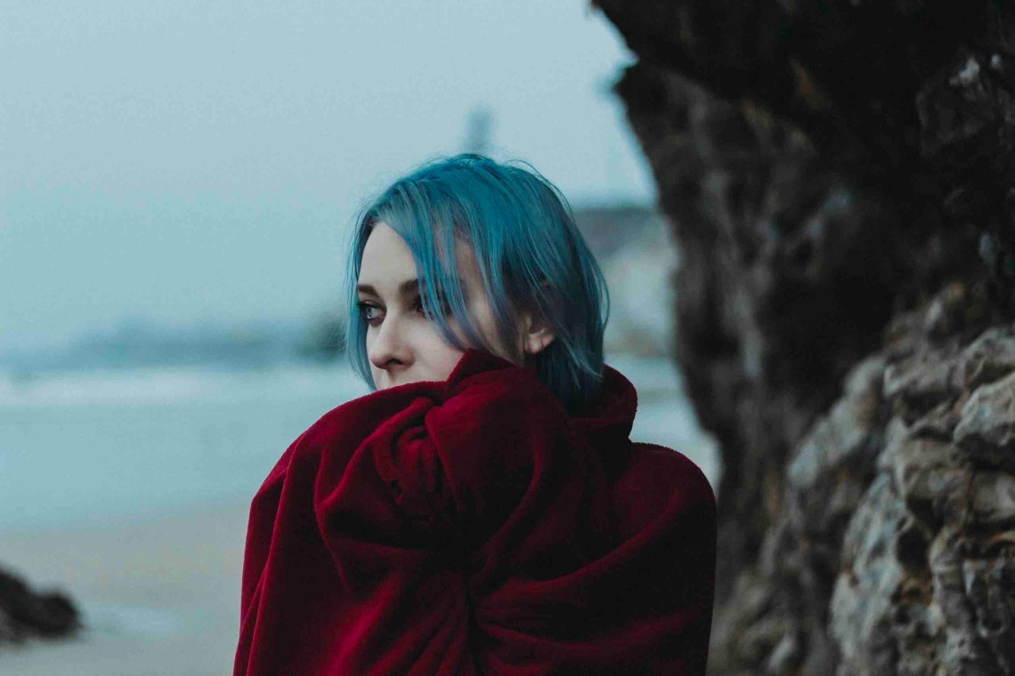 woman standing on beach with blue hair