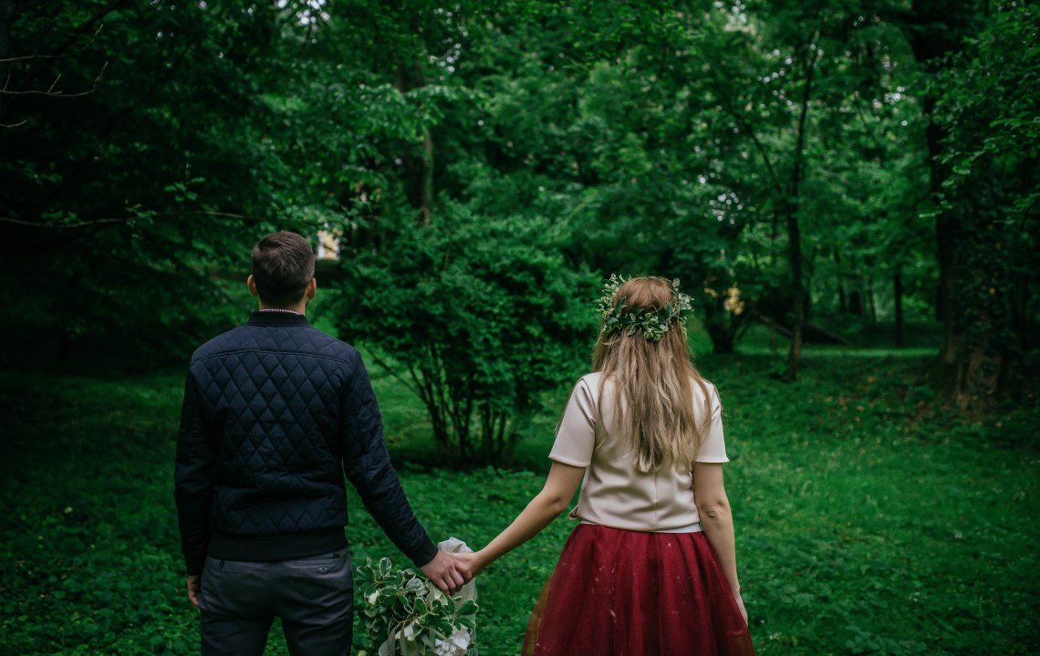 couple holding hands turning away from camera