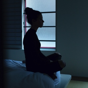 Woman's silhouette sitting in a dark bedroom