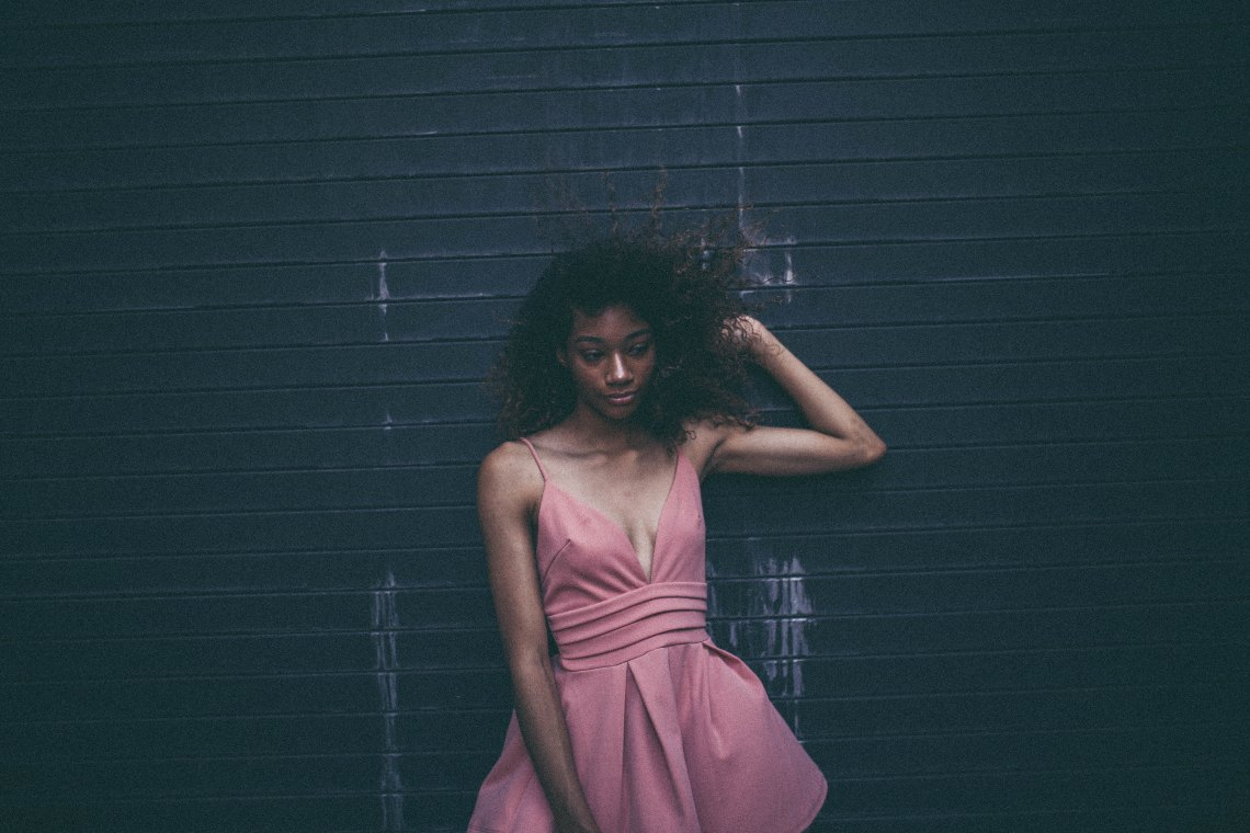 Woman in pink dress standing against wall
