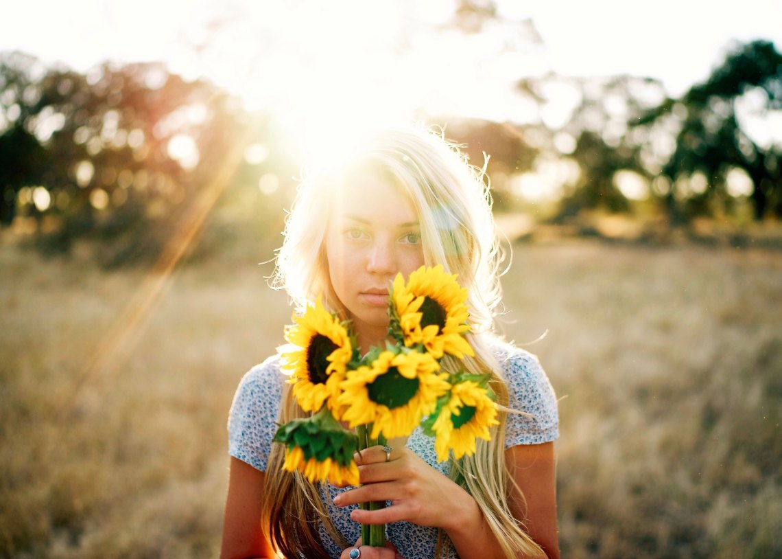 Blonde girl holding sunflowers in meadow