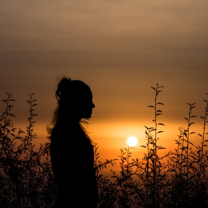 silhouette of woman in front of sunset