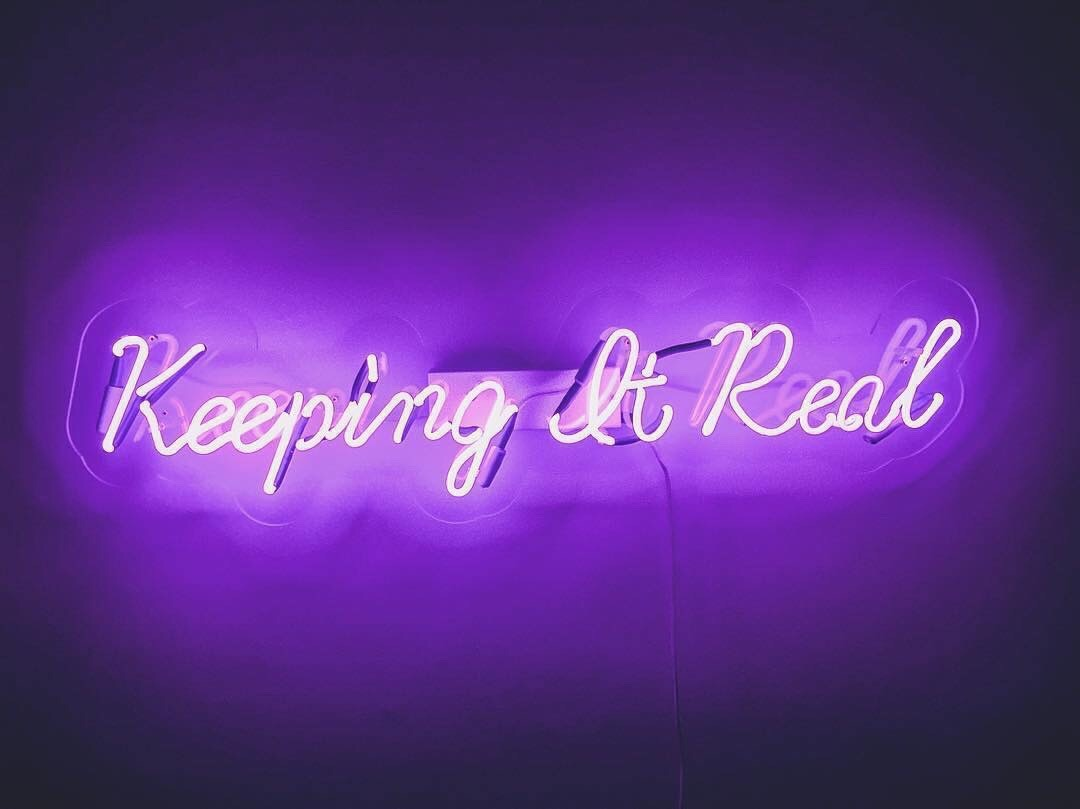 "Purple neon sign that says ""keeping it real"""
